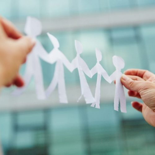 Hands holding business team made of paper